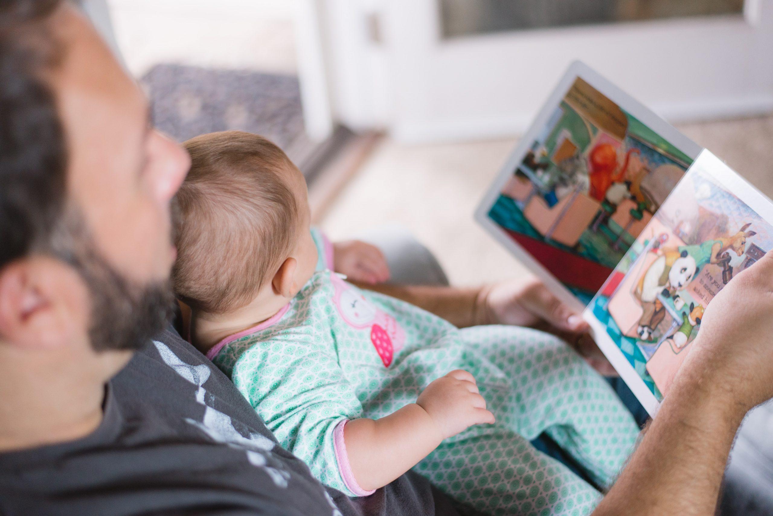 Pai e filho sentados. O pai conta uma história de livro para o filho.