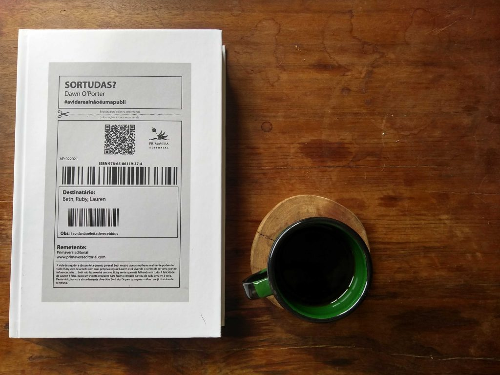 Livro Sortudas?, publicado pela Primavera Editorial; e uma xícara de café