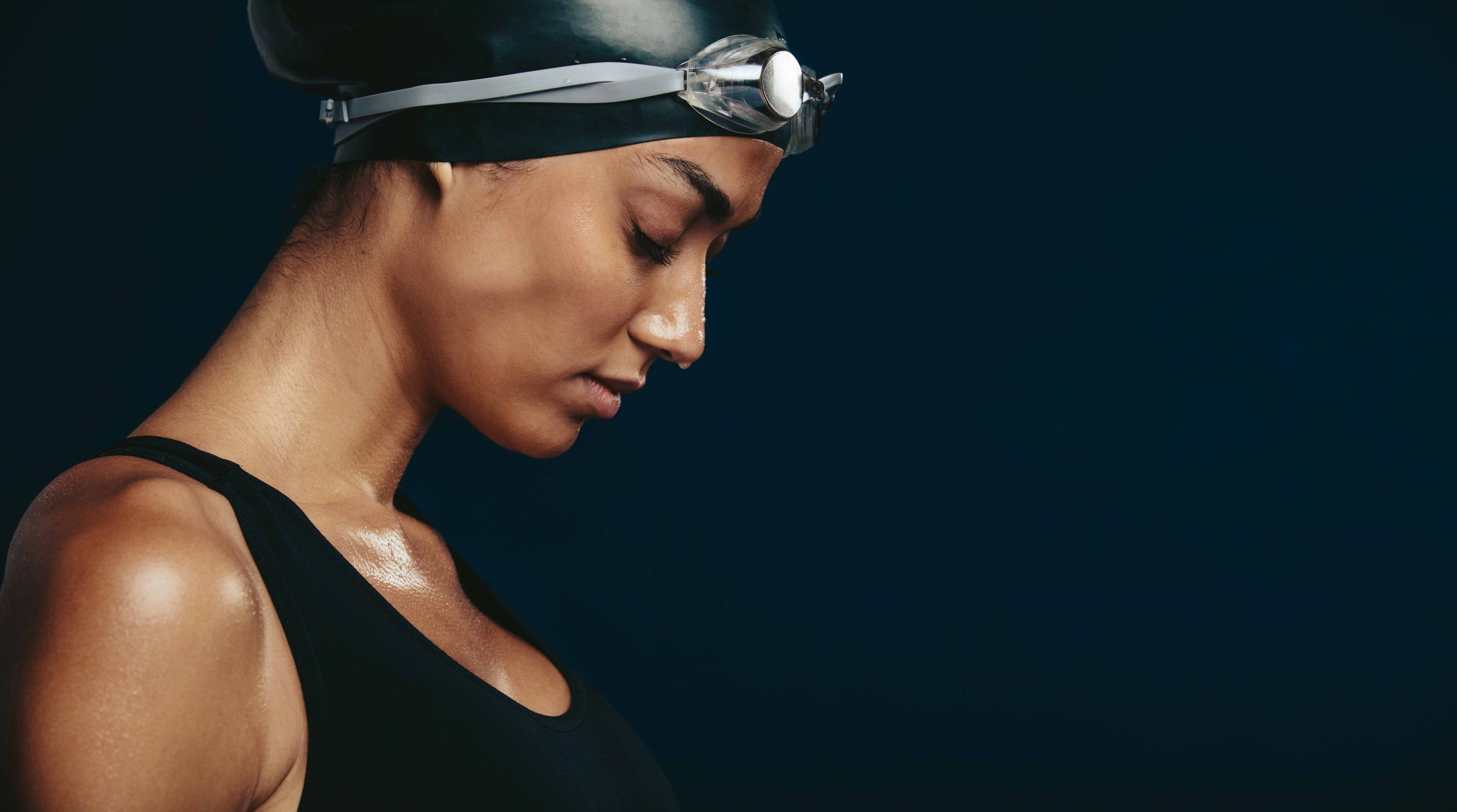 Toucas de natação para cabelos afro: Close-up of a woman swimmer looking tired after a race. Female wearing black swimsuit, swimming cap and goggles on dark background.